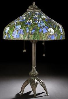 """An American patinated bronze and stained glass parlor lamp, by Bauer-Coble Studios, Art Nouveau style of Louis Comfort Tiffany, fitted with a large domed leaded glass shade in Iris decor, the interior fitted with four addorsed light sockets, the lamp base with six petaled feet, one with a copper logo plaque, another signed in script """"Bauer-Coble"""" dated 1979"""