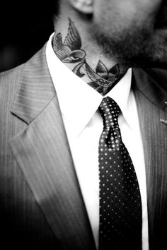 Man on a suit with swallow tattoo on neck