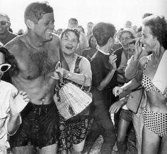 President Kennedy being mobbed by an adoring crowd as he emerged from the surf after a swim at Santa Monica beach near the home of his brother-in-law, actor Peter Lawford. The woman in the two-piece swimsuit exchanging grins with JFK was Eva Ban, and she got a lot of attention at the time. She lived in West Hollywood and was the wife of architect Alexander Ban. Photograph by Bill Beebe for the Los Angeles Times (August 19, 1962).