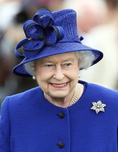 June 24, 2013:  Queen Elizabeth is wearing one of her favorite hats, a vibrant royal blue textured straw cloche style hat with a diagonal crown, cartwheel brim, and large looped bow. Via The Royal Hats Blog.