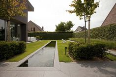 A long and narrow water basin is the main attraction of this minimalistic garden. Grote strakke tuinen | Filip Van Damme