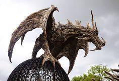 """James Doran-Webb, o escultor madeira flutuante incrivelmente talentoso que nós escreveu sobre anteriormente , expandiu seu trabalho de cavalos majestosos para aterrorizante dragões troncos que parecem preparados para aterrorizar o povo aldeia na paisagem circundante.  Doran-Webb criou dois épico escultura do dragão. A primeira, no cimo de uma árvore morta, é chamado de 'The Wyvern nos Baobabs' (a wyvern é um tipo de dragão com dois pés e duas asas). O outro, 'Folly de Wyvern, """"é empoleirado…"""