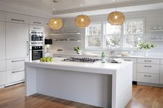 Modern cottage kitchen features white flat front cabinets adorned with oil rubbed bronze pulls topped with white quartz situated under white floating shelves lining a shiplap backsplash flanking three windows over a stainless steel sink and modern gooseneck faucet.