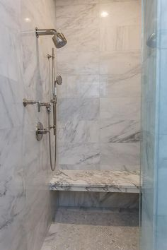 Beautiful walk in shower boasts a marble shower surround fitted with an exposed plumbing polished nickel shower kit and a marble bench floating over marble herringbone floor tiles.