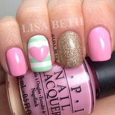 Pink nails, blue-gray and white stripe with pink heart, and gold glitter.