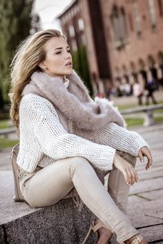 Molly Rustas wears neutral tones, pairing a beige scarf with a cream knit and matching skinnies. Brands not specified.