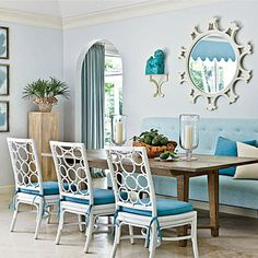 """The lady of the house requested that the formal dining room be set up around a banquette, a decision Howard supported wholeheartedly. """"It actually became my favorite piece in the house,"""" Howard says. """"I had it upholstered in China Seas's Java Java fabric and treated to be stain resistant, so it's easy to take care of."""" Get the Look: The table is from Mrs. Howard. The chairs are from Mecox Gardens."""