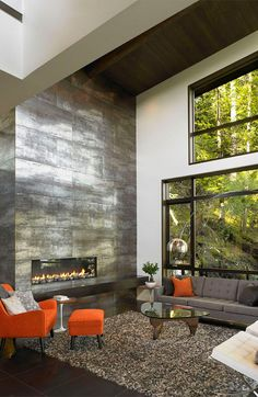 Steel Fireplace and large Windows in a high ceilinged living room.