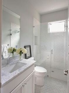 bathroom features a white vanity paired with a marble countertop over the gray arabesque tiled floor walker zanger avenue julia mosaic tiles