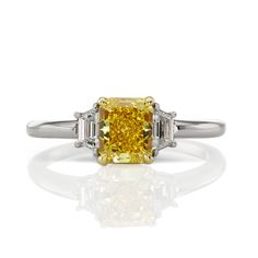 Sometimes, simple is infinitely better, like the trapezoid shaped diamonds flanking this gorgeous 1.18 carat fancy vivid yellow diamond in a traditional 3 stone setting | Scarselli Diamonds
