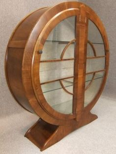 "A classic Art Deco furniture of the period. This beautiful circular china cabinet constructed of walnut and glass stands upon an outswept base and has twin opening doors. These open to reveal 3 internal glass shelves. The art deco round china cabinet has been lined during its lifetime with a beige material but would originally been the bare timber. The cabinet itself has been completely repolished in a traditional mellow walnut colour.  Height 52"" Width 47.5"" Depth 13.5"". @designerwallace"
