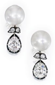 *PAIR OF PLATINUM, SILVER-TOPPED-GOLD, CULTURED PEARL AND DIAMOND EARCLIPS The tops set with two cultured pearls measuring approximately 17.5 by 17.4 mm and 15.6 by 17.0 mm, suspending two modified pear-shaped brilliant-cut diamond drops weighing 5.90 and 4.51 carats, respectively, further accented by eight old mine-cut diamonds weighing approximately .90 carat.