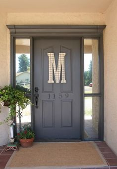 I keep looking at front door colors and though I love bright red and yellow and hello ORANGE it doesn't really go with my cream siding and blue shutters, but check out this dark grey. Now that's a color I love and could live with.: