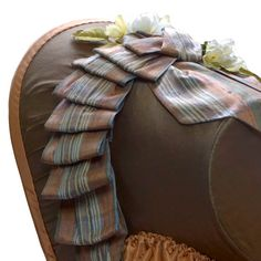 """1853-63 ___ Bonnet (reproduction) ___ Taupe silk taffeta exterior, peach silk taffeta lining and bavolet. Frame constructed of buckram and wire. Trimmed with silk shantung plaid ribbons and artificial flowers. ___ Bonnet shown on a 21"""" foam head and is recommended for head sizes 21 – 22"""". ___ Bonnet Dimension: Height 11"""", Width 9"""", Depth 8"""" (top of the brim to tip), Ties 39"""" long ___ Excellent for a middle class impression. ___ photo 4"""