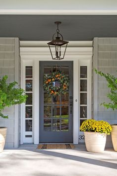 Grey front door surrounded by flower pots
