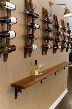 Creating a wine bar when you don't have the space: Stylize a blank wall. This extra wall was wallpapered with burlap with hung with repeating store-bought wine racks. A walnut ledge offers a place for glasses during tastings. Lighting above illuminates the labels.