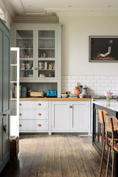 """Lowe chose a combination of deVOL's Classic English and Real Shaker cabinetry, shown side-by-side above. """"The simplicity of the Shaker pieces were perfect to soften the bold and busy marble on the island,"""" said Parker. The marble is arabescato vaglia."""