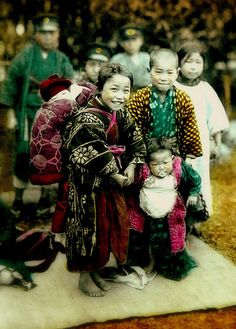 Smiling young Japanese girl with a baby on her back, and two boys. By an anonymous photographer on the streets of Japan. Ca.1900