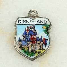 This is an image of the vintage Disneyland souvenir shield charm's front.