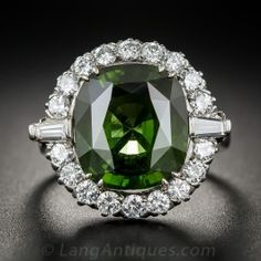 8.50 Carat Green Zircon and Diamond Ring  - Reminiscent of the color of chrome tourmaline, but considerably rarer, this glorious green zircon, weighing 8.50 carats, is featured in a gleaming 18k white gold ring framed with a halo of bright-white glittering diamonds, punctuated where the shank meets the crown with slightly tapered, bar-set, baguette-cut diamonds. Measuring 11/16 inch in length and 13/16 inch in width, this very special jewel makes a grand presentation. Size 9 1/2.