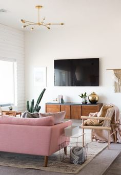 living room with pink couch and natural light | bright white living room