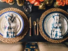 For proper balance, use one dominant color throughout the tablescape. In this dining room, the dominant color in the dinnerware is navy blue. Since the complement to blue is orange, antique floral plates with layered shades of orange, pink and coral are used as well-balanced accents.