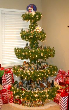 Another pinner wrote: This is a Christmas Tree my husband built for me. I am able to use all my lighted houses. It has electric plug ins running up the middle pole.