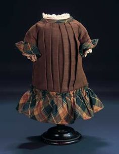 "Brown Woolen and Plaid Woolen Dress 4 1/2"" shoulder width. 10"" overall length. To fit child doll about 16"". Of brown wool,the dropped-waist dress has front pleats that center the front closure with pearl buttons disguising the hook and eye closures,having plaid wool ruffle at the hem,neckline and forming the edge of the short sleeves. There is a lace ruffle at the neckline and sleeve bands. Excellent condition. Circa 1885."