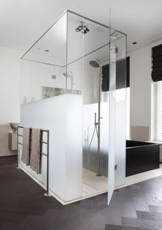 Stunning Bathroom - love the frosted panes for the shower & the black bathtub. Love the floor plan & how the shower backs up to the bathtub & is in the center of the bathroom with space to walk around the outside of the shower & tub.