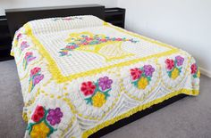 Gorgeous white & yellow chenille bedspread. Features bright pink, purple and yellow flowers in a yellow basket in the center. Bedspread