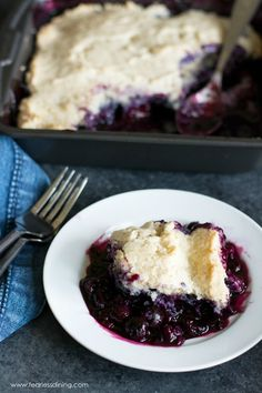 A serving of gluten free blueberry cobbler on a white plate. The dish of cobbler is behind the plate.