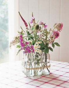 Creative Flower Arrangements - A grouping of bottles, filled with wildflowers and tied together with twine