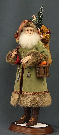 Santa Doll (Santa di Olivia): Ball-jointed neck & wrists with wire armature limbs. Mouth-blown glass eyes. Hand made, original costume of fine velvet, brocade, & designer quality faux fur. Hand-sewn shorn Leicester lamb's wool wig & beard. Fur-trimmed cap coordinates, Hand-made leather belt with metal charms. Silk toy sack with miniature toys & Flocked Tree. Basket is filled with hand-made oranges / Jim Cardoza, Bruce Henderson, & Kat Soto for Shreve & Company © 2010 The Dollsmith