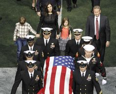 Taya Kyle (rear) and her children walk behind the coffin of her slain husband former Navy SEAL Chris Kyle during a memorial service for the former sniper at Cowboys Stadium.