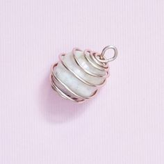 Affordable wire wrapped, light pink polished stone pendant. Measures 1in (2.5cm) x .75in (1.9cm).