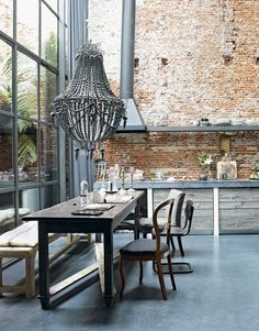 loft style kitchen with very high ceilings, exposed brick wall,large beaded chandelier over wood table. Industrial chic look Interior Design Blogs, Brick Interior, Modern Interior, Interior Photo, Kitchen Interior, Interior Ideas, Interior Decorating, Decorating Ideas, Living Etc