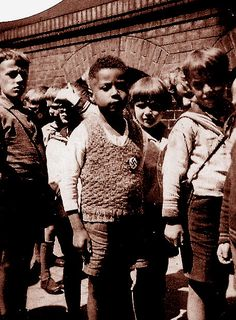 """""""Growing Up Black in Nazi Germany"""", Born in 1926, Hans Massaquoi was the child of a German nurse and a Liberian diplomat. When he was in second grade, Hans was so taken with the Nazi imagery that, at his request, his nanny sewed a swastika to his sweater. Although his mother removed it when he returned home from school, a picture had already been taken."""