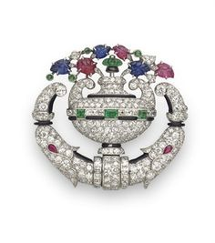 AN ART DECO DIAMOND AND MULTI-GEM LAPEL WATCH, BY TIFFANY & CO.  Designed as an openwork single and circular-cut diamond vase, extending carved ruby, sapphire and emerald leaves, with French-cut diamond, square-cut emerald and black enamel detail, the reverse watch, of mechanical movement, the oval cream dial with black Arabic numerals and blued-steel hands, within a wide platinum bezel, mounted in platinum, circa 1925 Signed Tiffany & Co., no. 32760