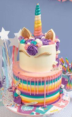 idee für eine zweistöckige einhorn torte mit einem weißen horn mit einem langen regenbogenfarbenen horn und mit einer mähne aus lila und kleinen blauen und pinken rosen   idee für einhorn kuchen deko