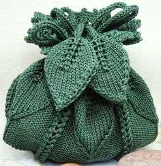 Pretty dark  green knitted pumpkin purse with leaves.