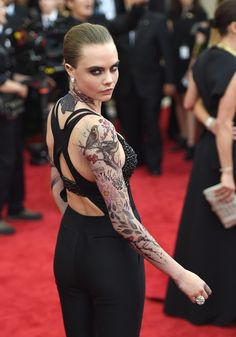 Cara Delevingne showed up at the Met Gala last night with two full sleeves of tattoos. | Cara Delevingne Wore Full Tattoo Sleeves To The Met Gala- Beautiful Design!!!