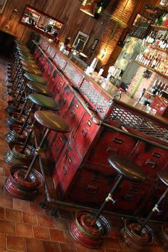 traditional terracotta tiled floor with brick wall in background. the red distressed bar seems to be made from old filing cabinets and the stools complement the colour of the bar well.: