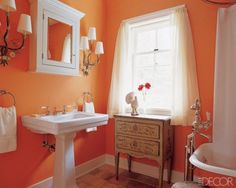 Cantaloupe color bathroom. Pair with leopard print vanity with jade knobs. Gold trim mirror. Whit subway tile. Navy stripe curtain. Smudge brass sconces?