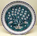 Turchia, periodo ottomano, piatto con prugnolo in fiore su sfondo colorato, iznik, 1550-1600 ca.jpg