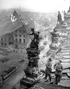 Red Army soldiers place flag on Reichstag building in Berlin, 30 April 1945.  Multiple banners and flags were hoisted on the Reichstag, many shot down as the battle continued.  Photo: Sovfoto