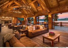 Love the indoor to outdoor flow of a living room like this, minus the huge fireplace and antler chandeliers, and massiveness