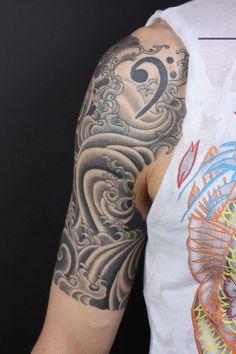 tatouage homme bras: clef de fa et vagues stylisées