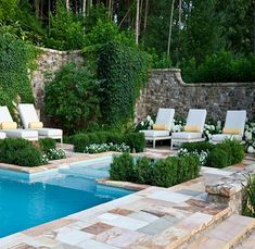 Beautiful pool deck and patio area with natural stone tile and planters flanking the pool.  M t many colors