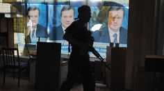 A Russian fighter walks past pictures of Ukraine's ousted ex-president Viktor Yanukovych in the eastern city of Donetsk on May 29, 2014