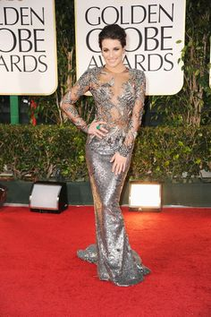 Lea Michele turned on the shine in a silver gown with a daring peek-a-boo bodice and a sequined skirt. The queen of the red carpet pose accessorized the look with a bold green cocktail ring and dramatic smoky eye makeup.